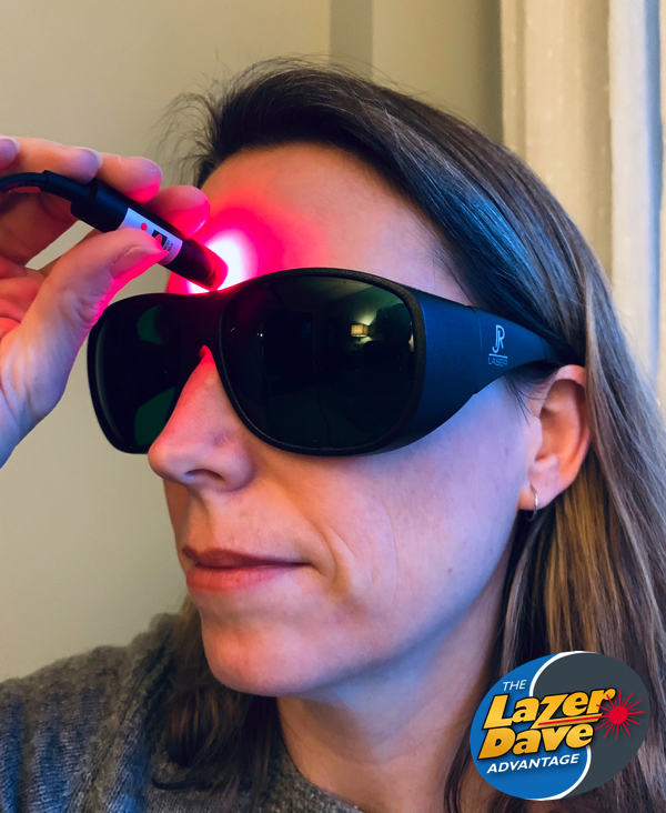 Woman treating herself with a low intensity laser device for alcohol addiction.